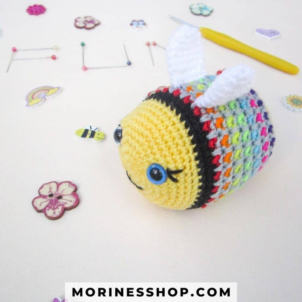 Rainbow Bee is a free crochet bee pattern perfect for spring. It uses moss stitch to achieve beautiful colourwork through most of the body. #CrochetBee #BeePattern #CrochetBumblebee #CrochetAmigurumi #AmigurumiBee